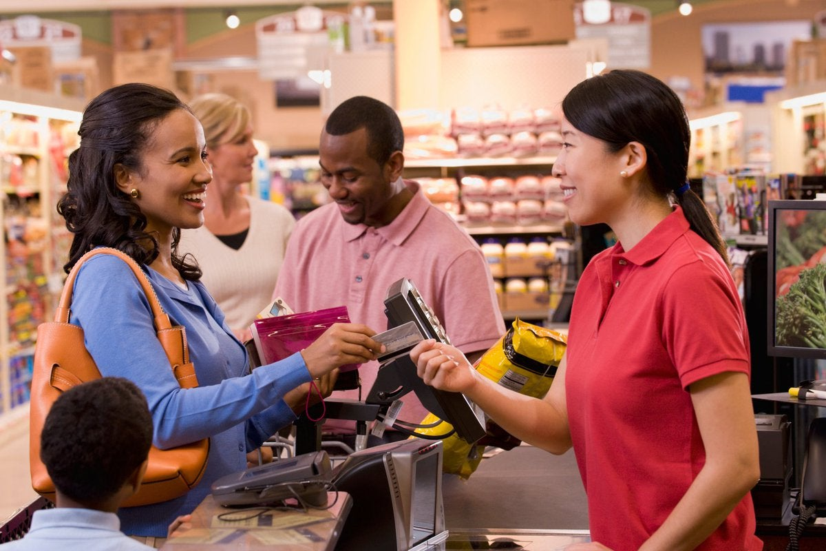 Smiling parent handing credit card to cashier