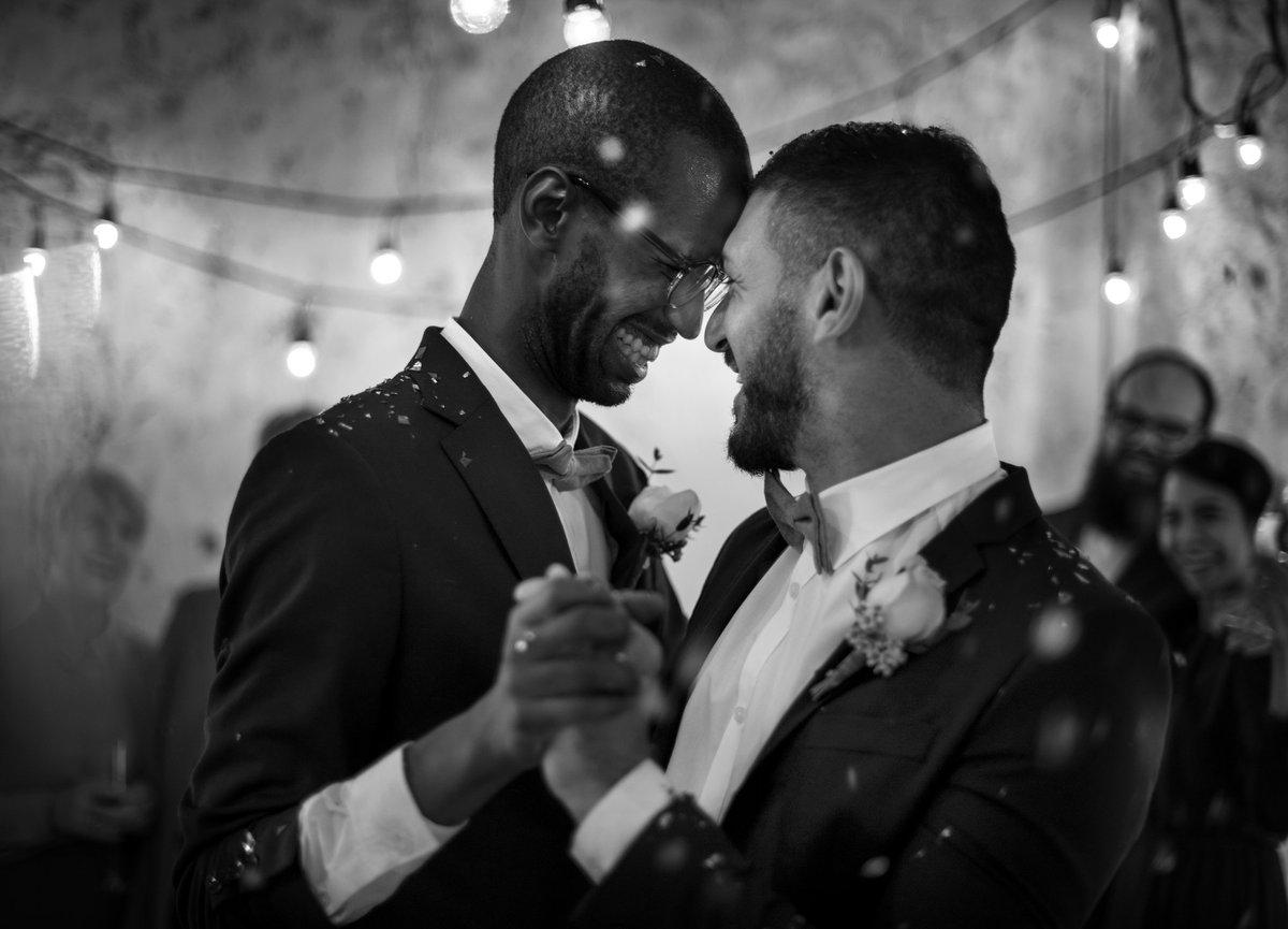Smiling men dancing at their wedding