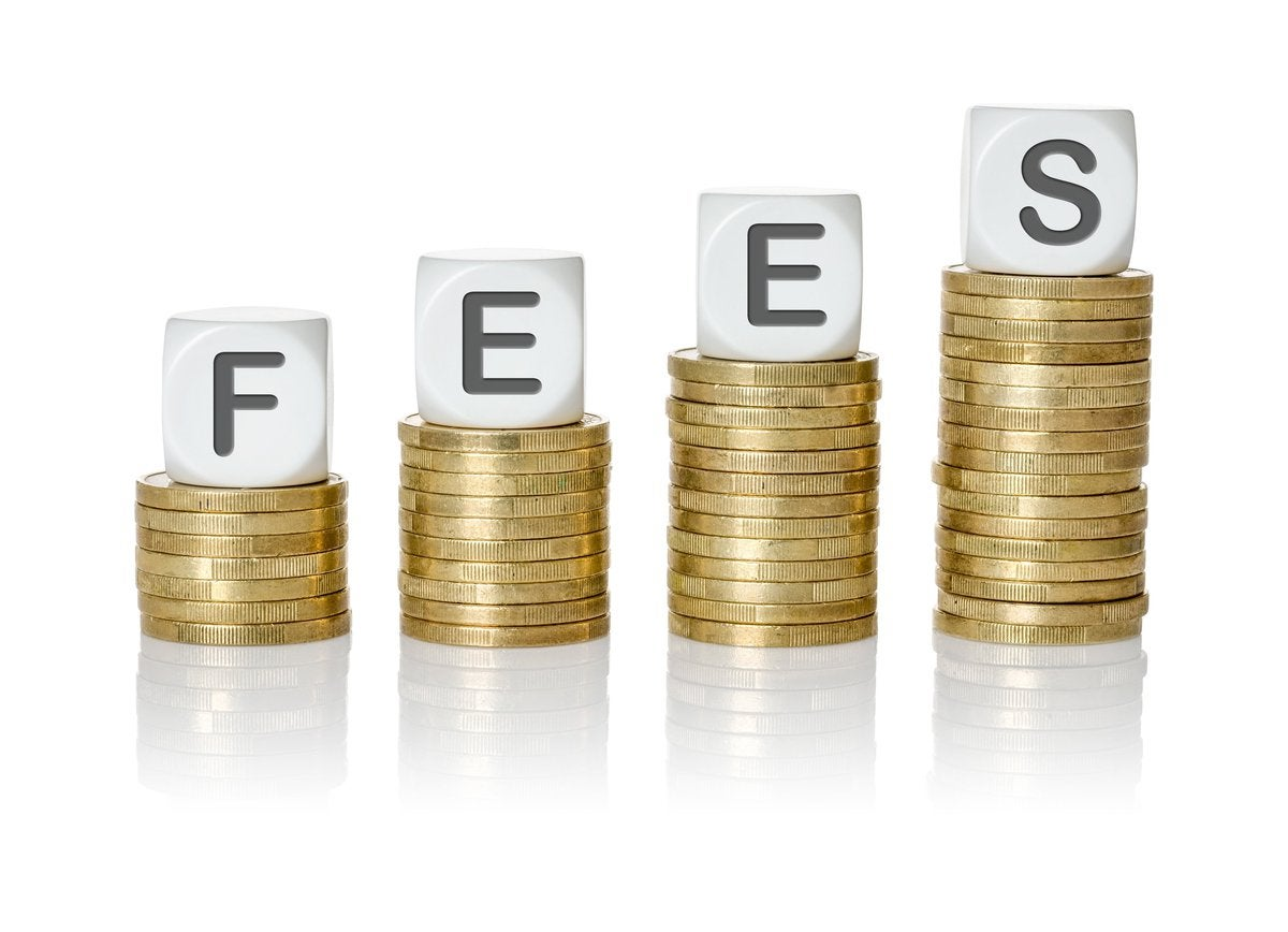 Stacks of coins in increasing size with blocks spelling the word FEES atop the piles.