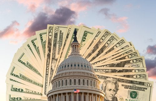 $20 bills fanned out behind the U.S. Capitol building.