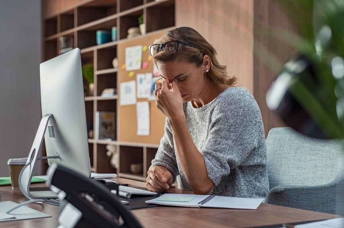 A stressed woman sitting at a desk in an office.