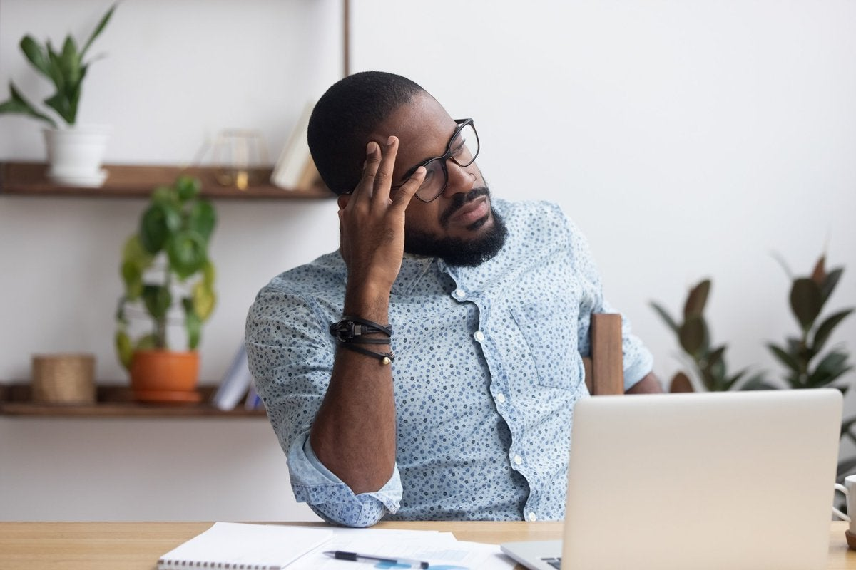 A stressed man sitting at a desk with his hand on his forehead.