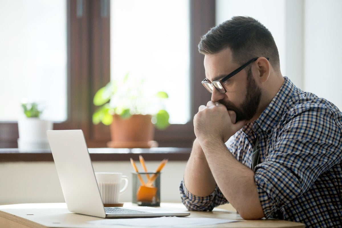 A stressed man sitting at a desk in front of an open laptop with his chin in his hands.