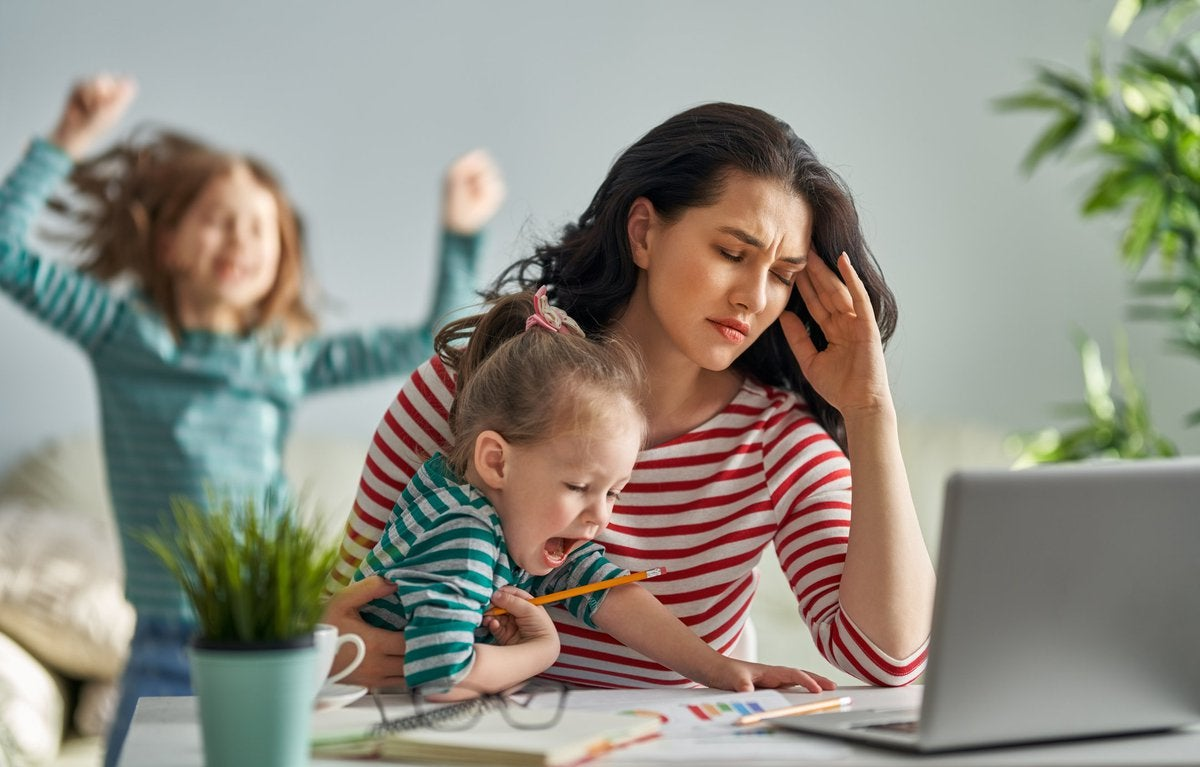 A stressed mom trying to work on her laptop while her kids distract her.