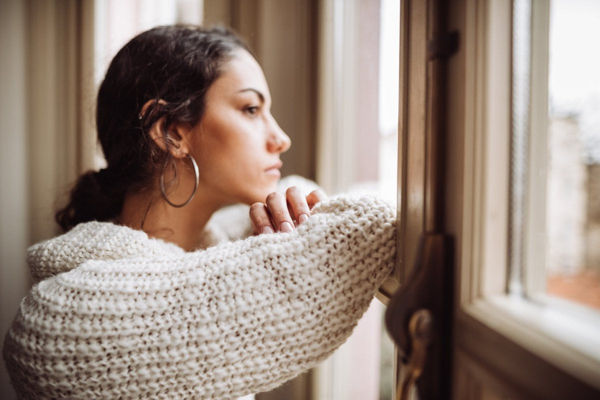 A stressed woman staring out the window with her head resting on her folded arms.