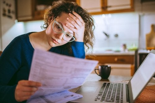 A stressed woman sitting in front of a laptop at her kitchen table and looking at bills in her hand.