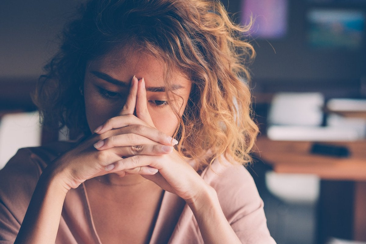 A stressed young woman with her hands on her face.