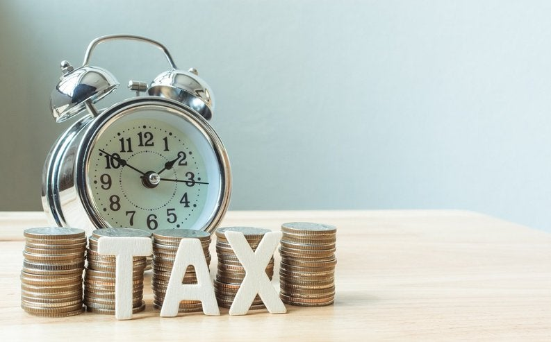 """A pile of coins spelling out """"Tax"""" stands in front of a clock."""