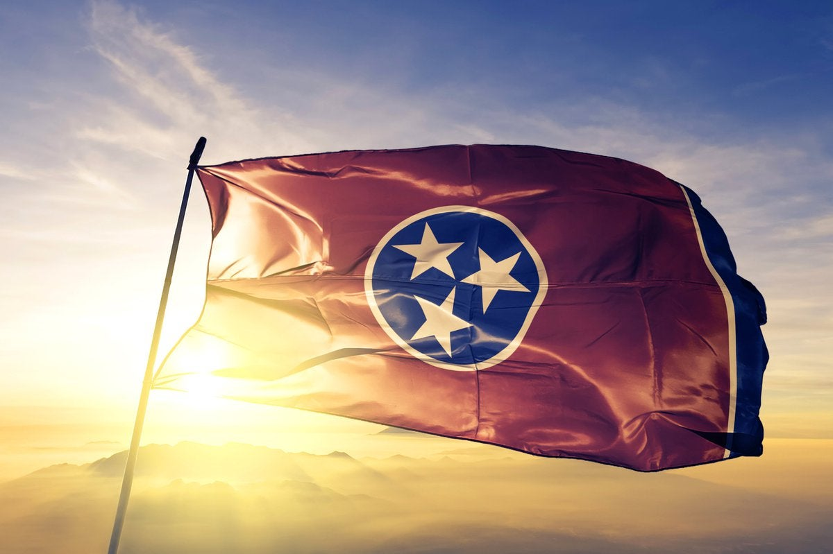 The Tennessee state flag flying in front of a sunny sky.