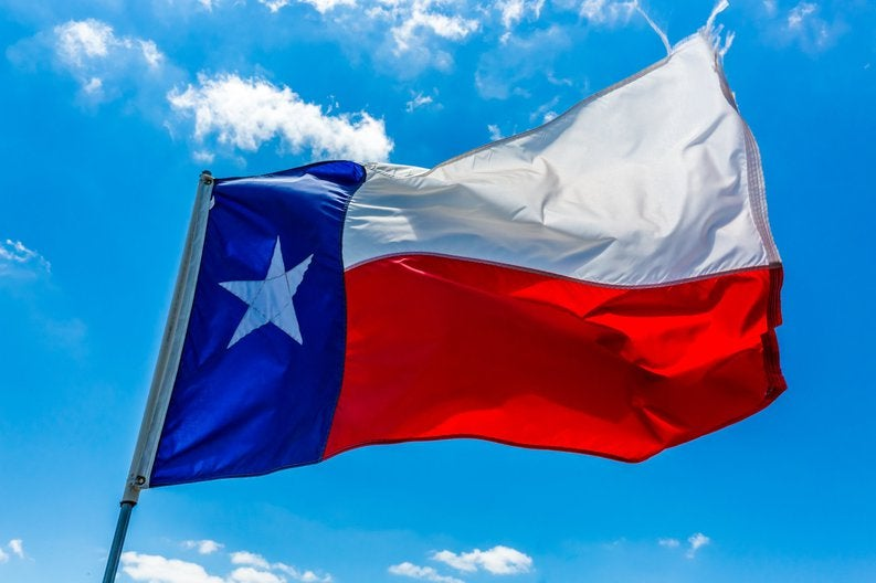 The state flag of Texas flying in front of a bright blue sky.