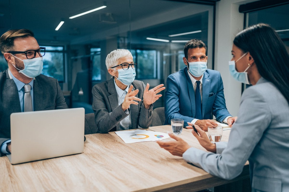 Three masked professionals interviewing masked woman in office setting.