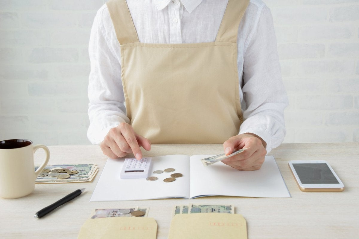 Person In White Room Organizing Coins And Bills While Using Calculator