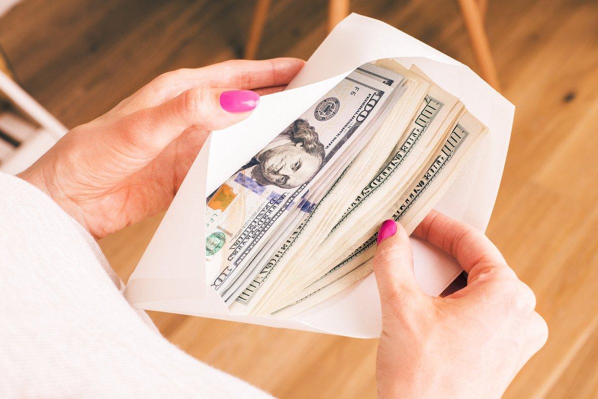 Woman holding envelope full of hundred dollar bills.