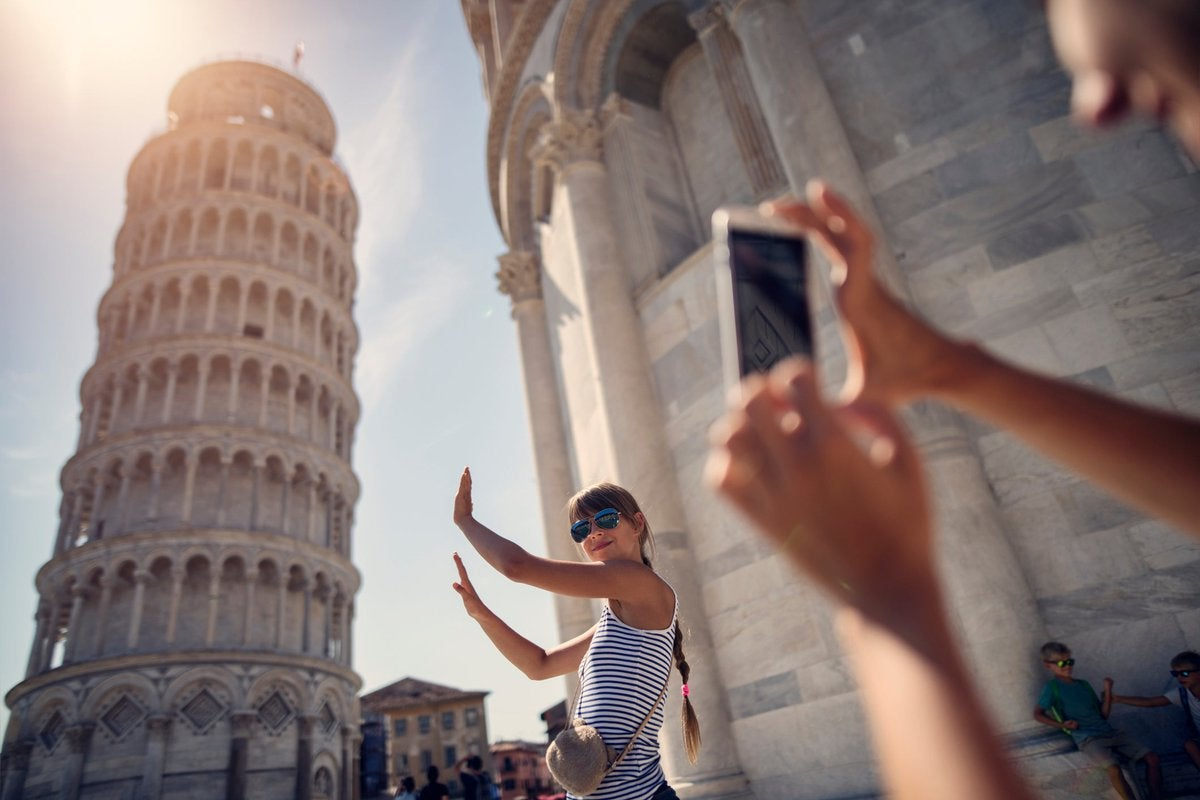 Tourist taking selfie with the leaning tower in Italy.