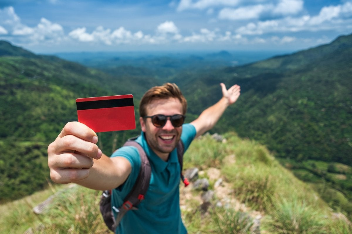 Traveler with credit card in mountains