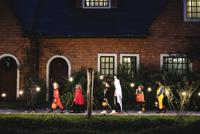 Trick-or-treaters walking in a line in front of a house.