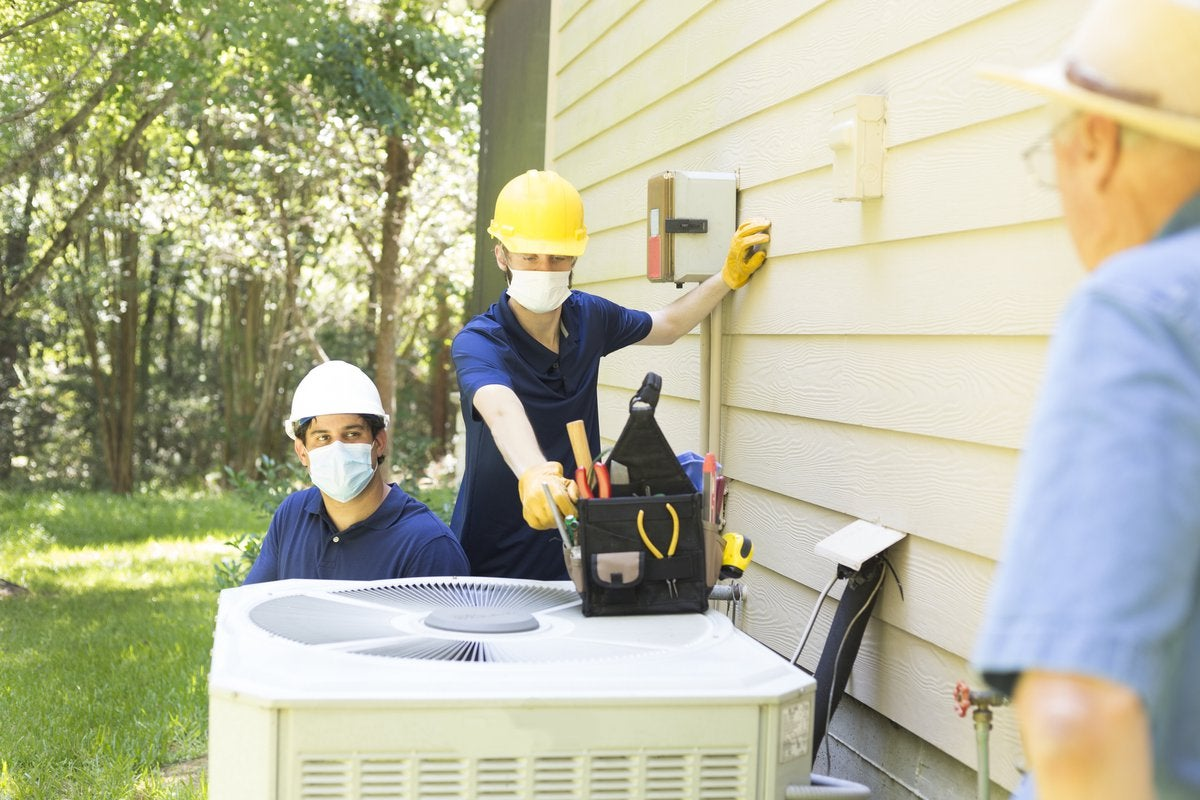 Two air conditioner workers service outside unit.