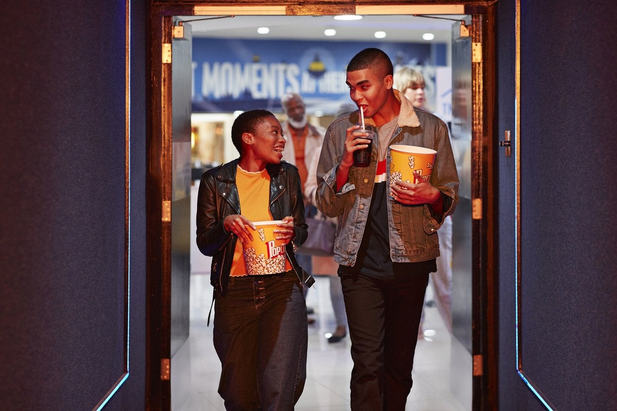 Two smiling friends head into a movie theater.