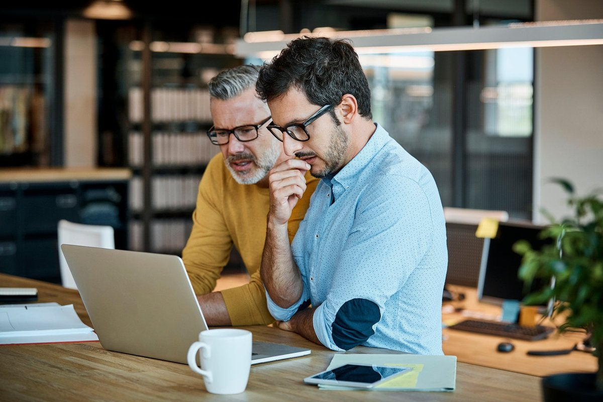 Two men in thought looking at a laptop screen together.