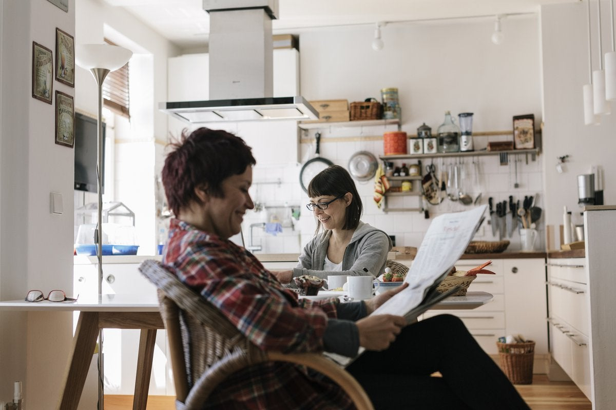Two people in a kitchen reading the news.