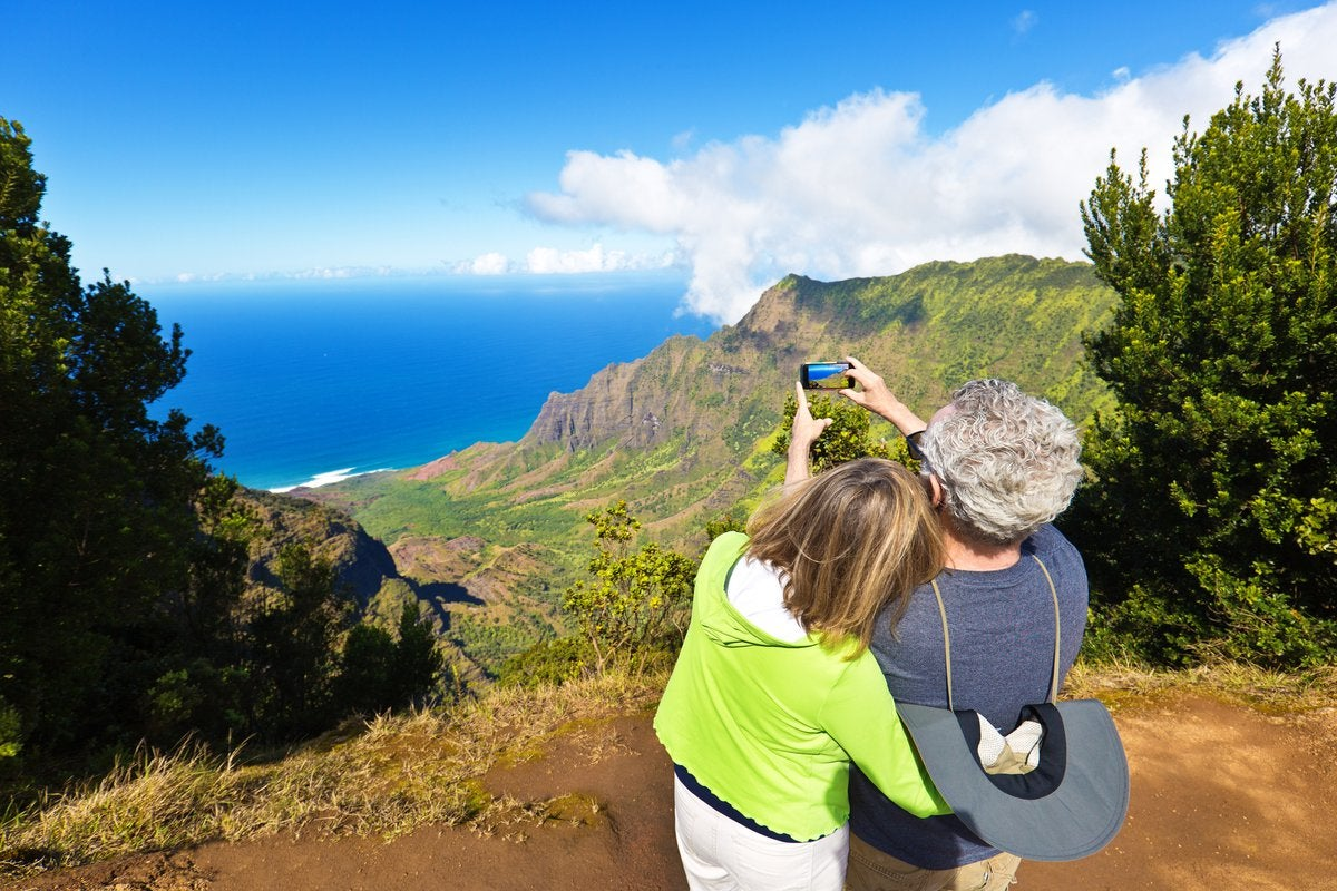 Two people taking photos at a scenic overlook featuring oceans and green hills