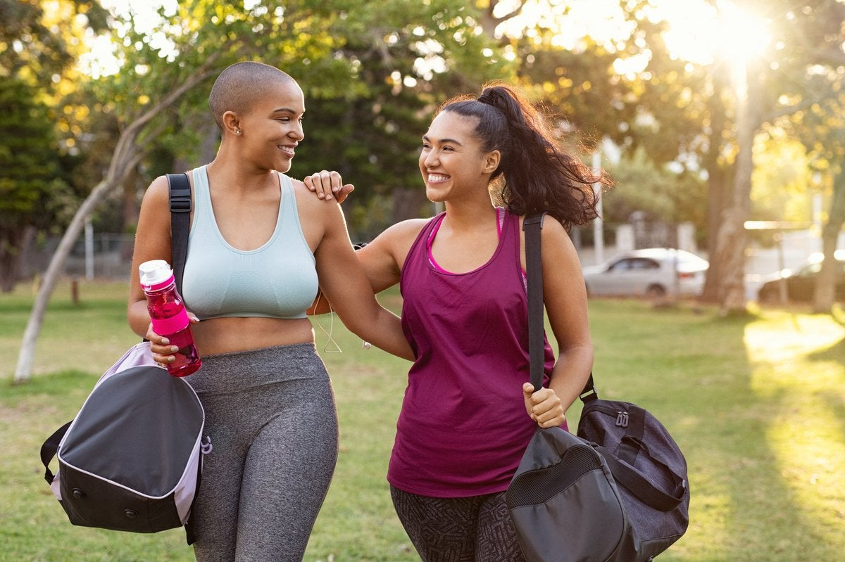 Two smiling women wearing exercise gear and walking in a park.