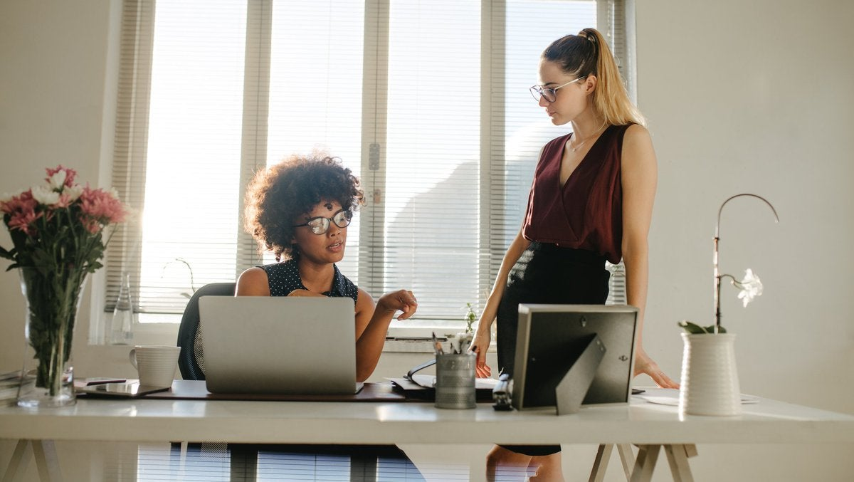 Two businesswomen having a discussion in an office.