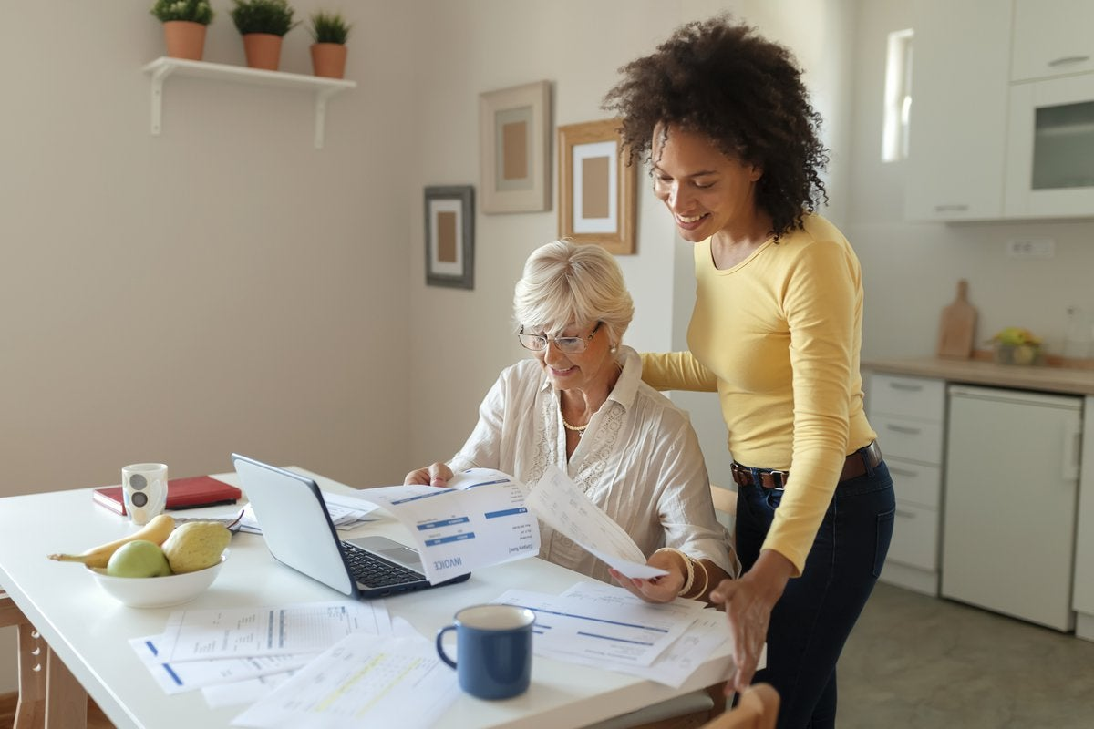 Two women are in a kitchen. One sits as the other looks over her shoulder, helping with personal finances.