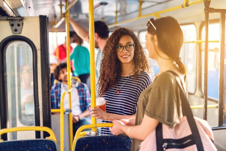 Two women chatting while standing on a sunny bus.
