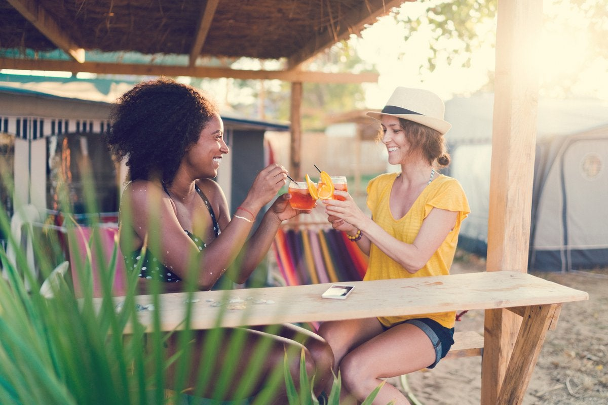 Two young adults enjoying cocktails in a tropical setting.