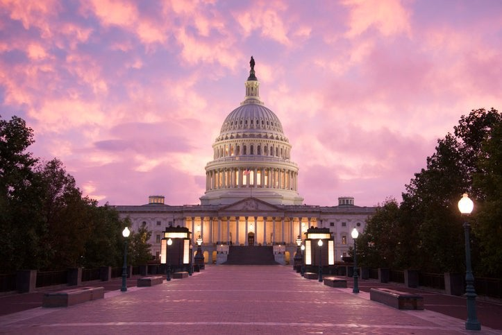 The United States Capitol building in front of a pink sunset sky.