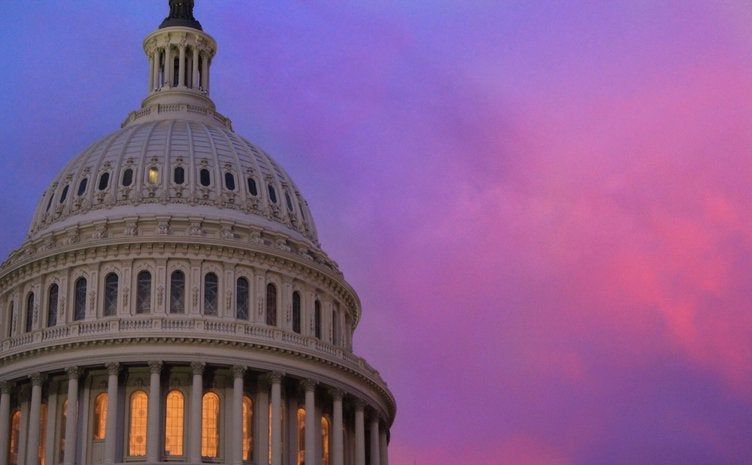 The rotunda of the United States Capitol building in front of a pink and purple sunset sky.