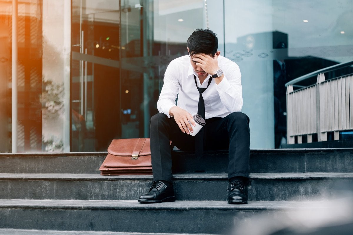 Devastated business man sitting on steps outside of building.