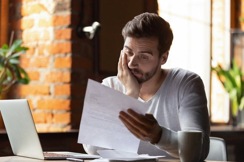 A distraught man sitting at his desk and reading bills with his chin in his hand.