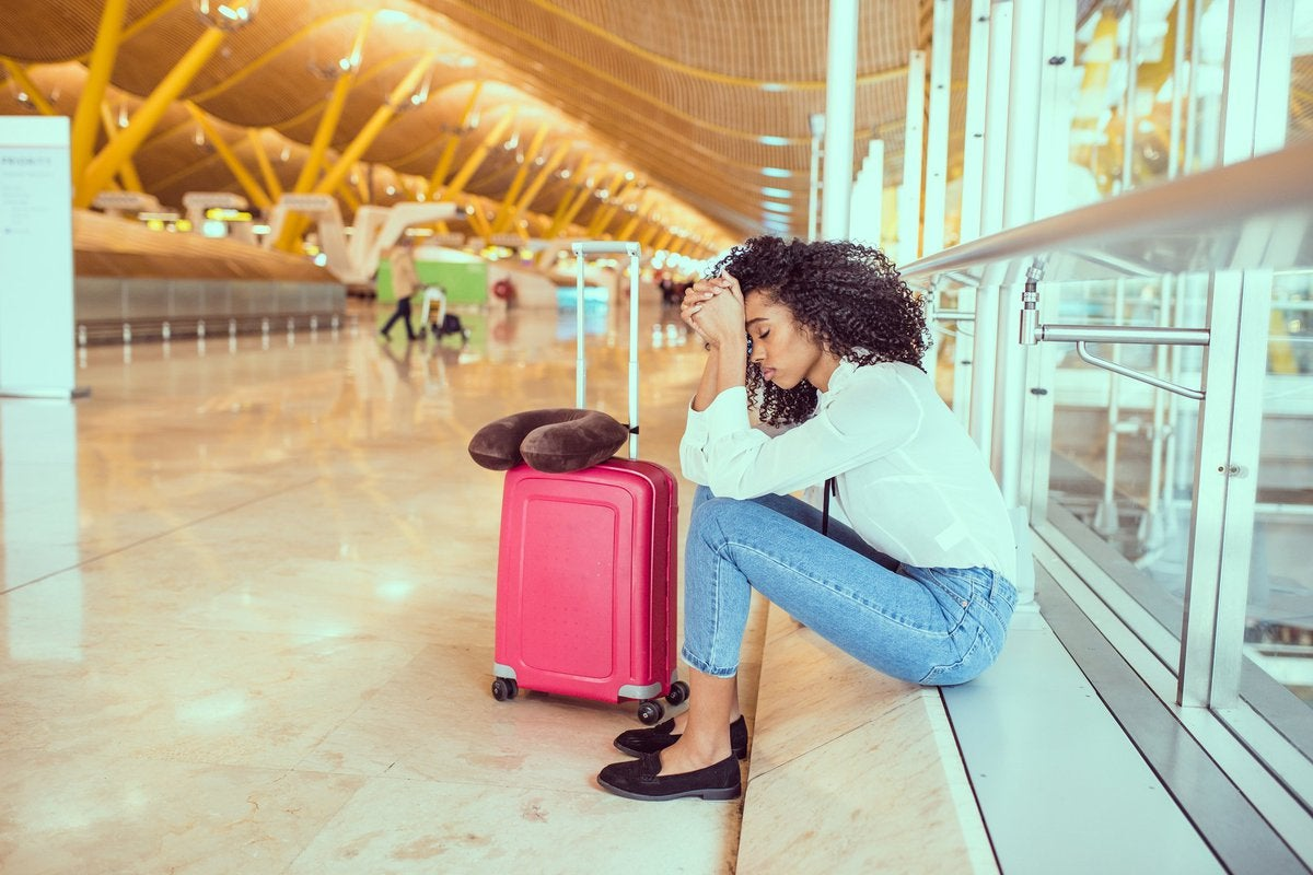An upset woman sitting next to her suitcase at an airport.
