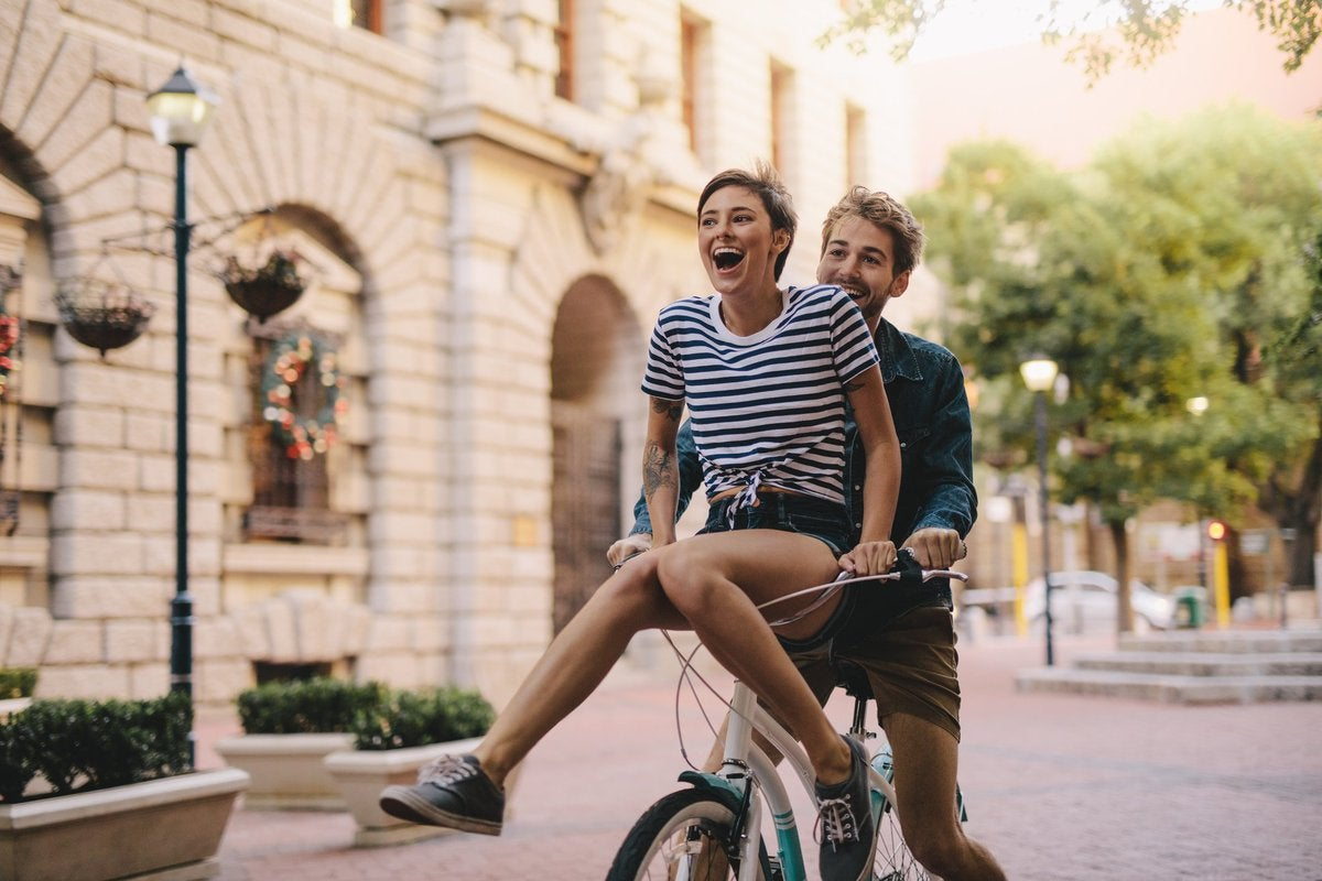 A laughing young woman riding on the handlebars of a bike being pedaled by a young man.