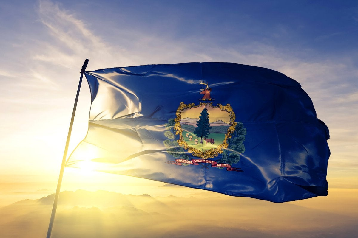 The Vermont state flag flying in front of a sunny sky.