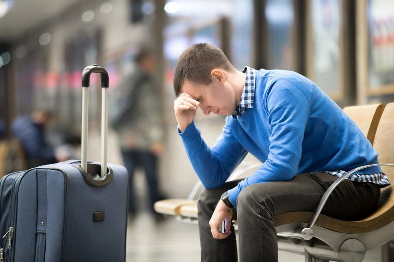 Dejected man sitting at airport beside his luggage,