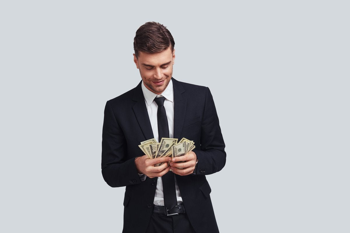 Wealthy man in a suit counting money.