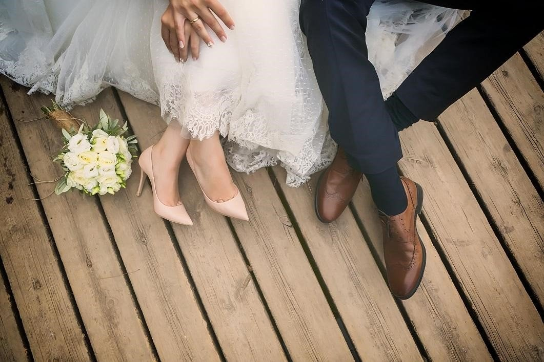 Bride and groom shown from the knees down holding hands while sitting