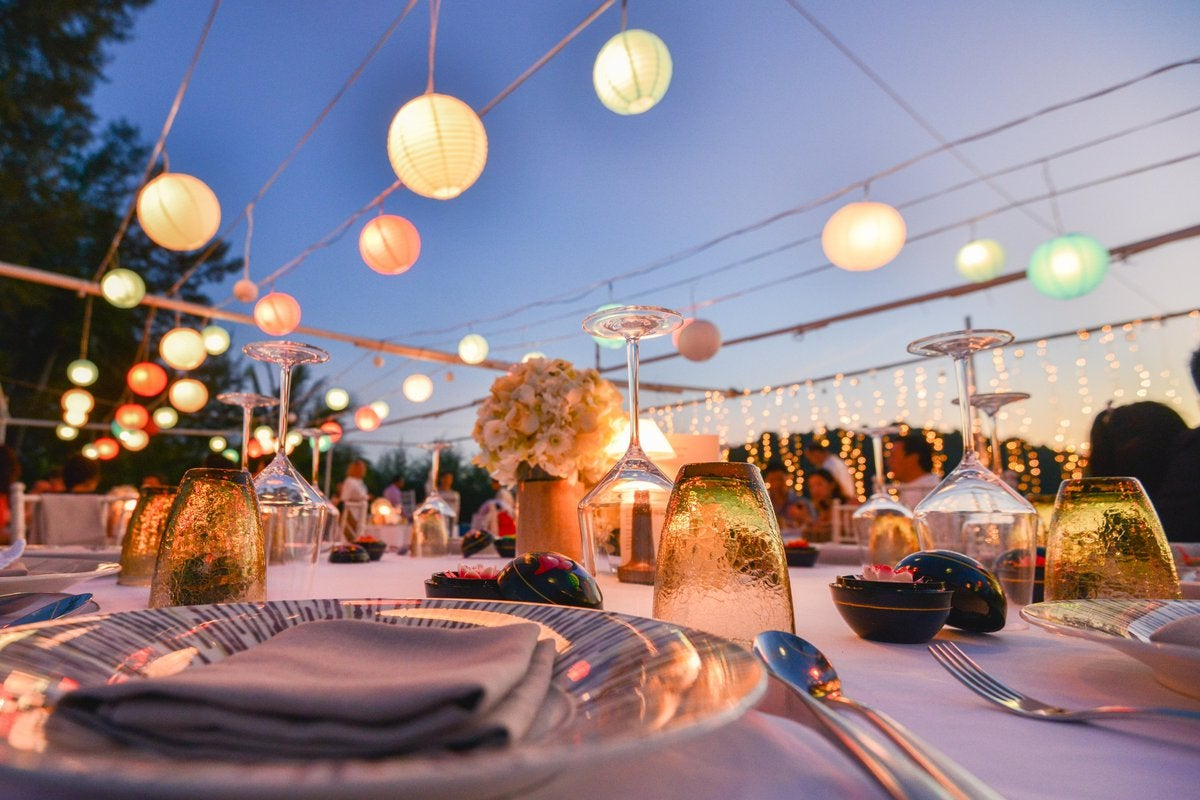 Outdoor table settings at a wedding under paper lanterns