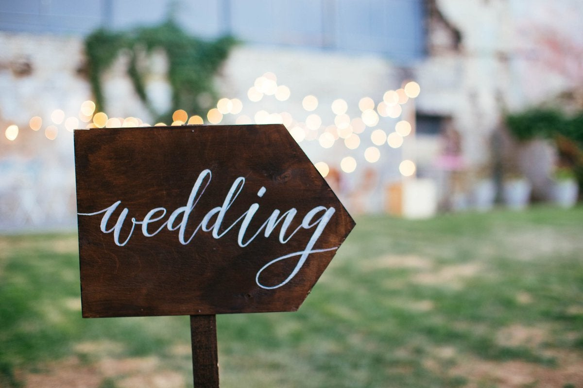 A hand-painted wedding sign pointing towards a lawn lit up with twinkle lights.