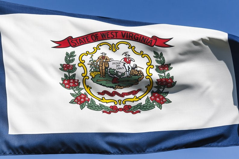The West Virginia state flag flying in front of a blue sky.