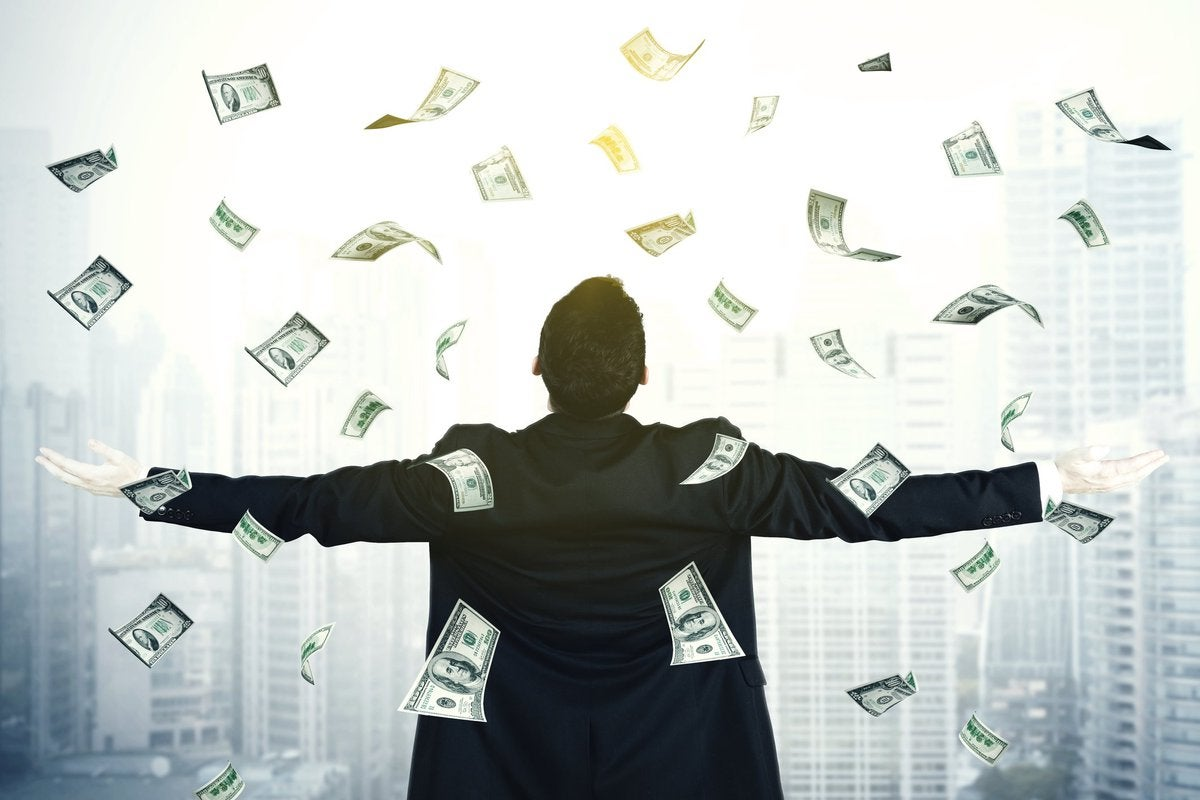 Man with arms outspread and cash raining down on him.