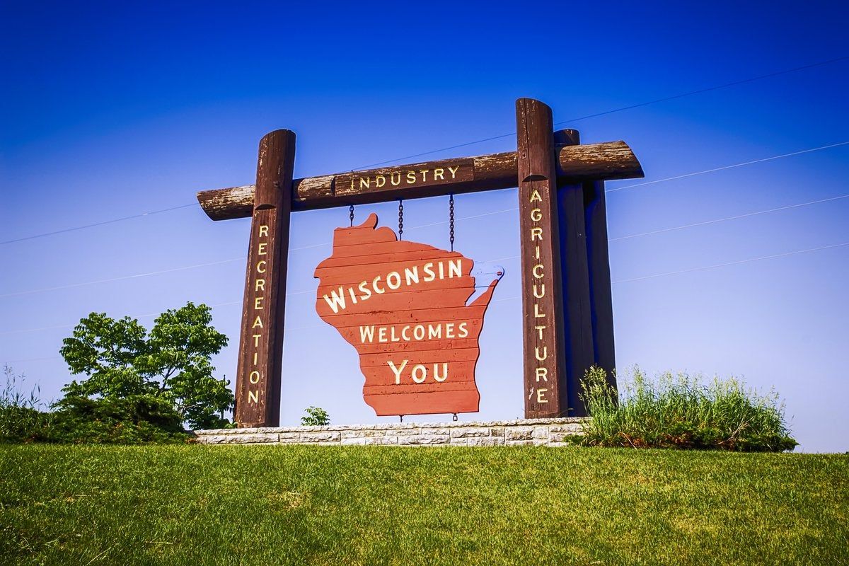 A large road-side sign surrounded by green grass and a blue sky welcoming visitors to Wisconsin.