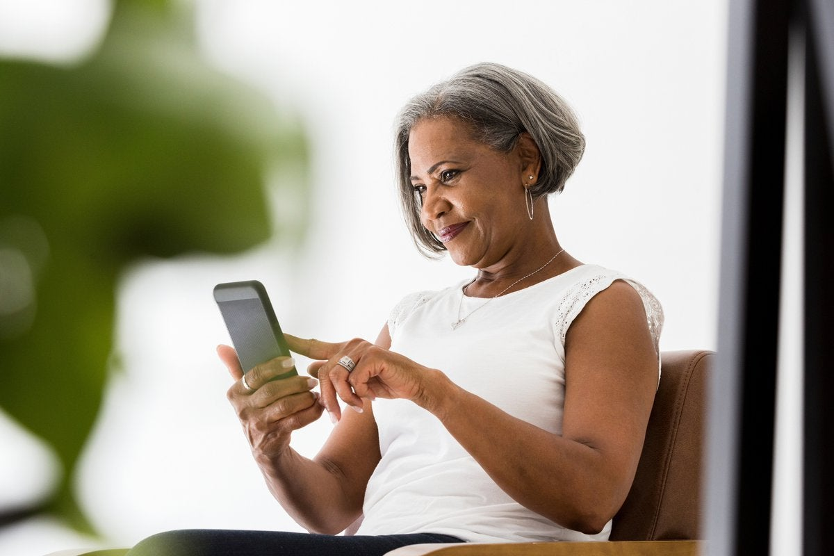 A woman sits and looks at her phone while smiling.