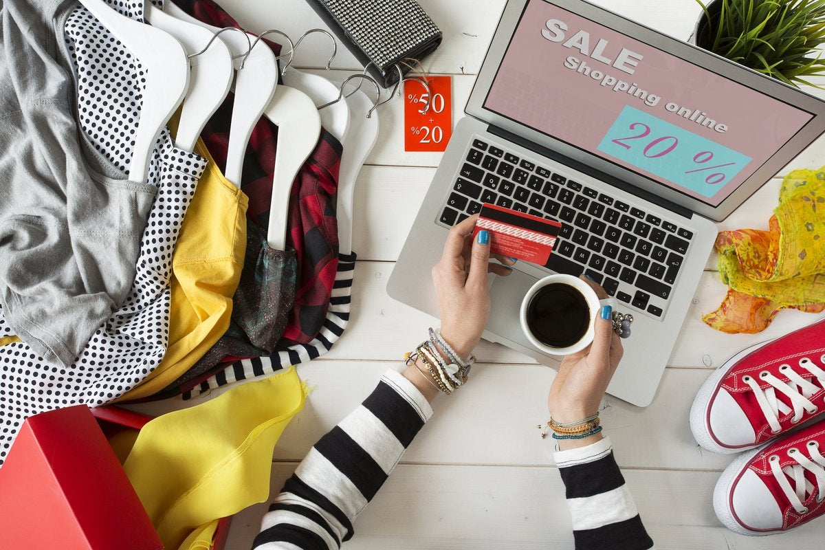 Woman at a laptop surrounded by shopping items