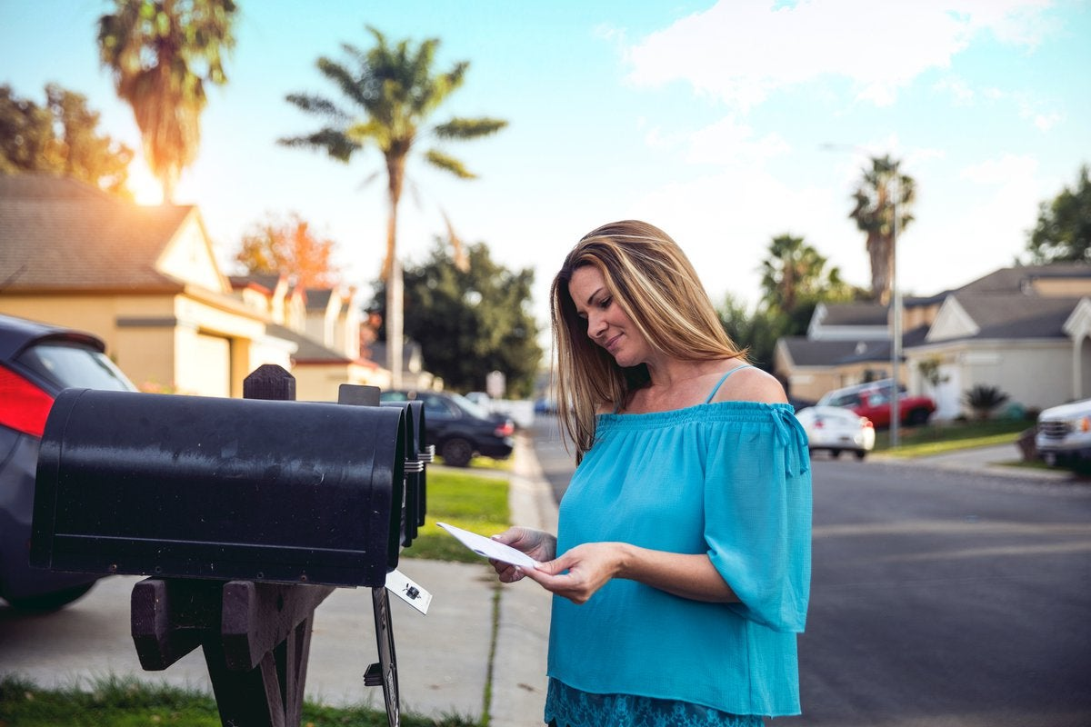 Woman checking mailbox in neighborhood with palm trees.