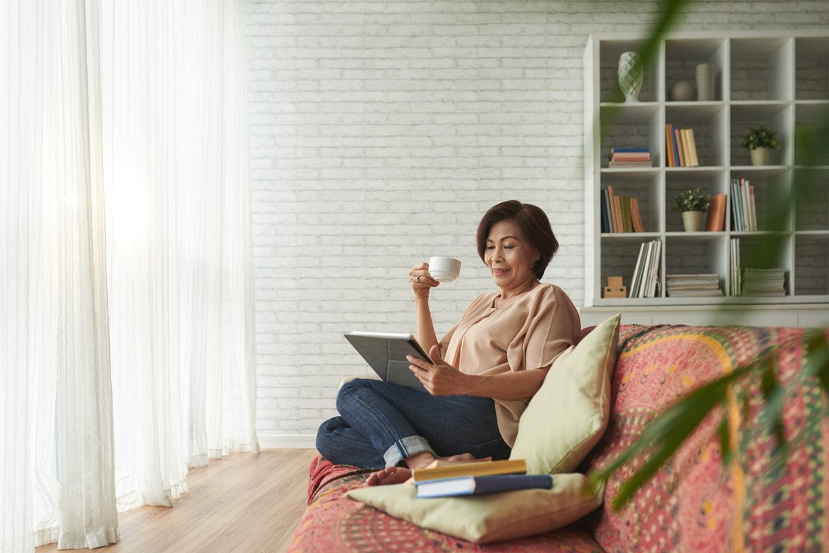 A woman drinking coffee on her couch.