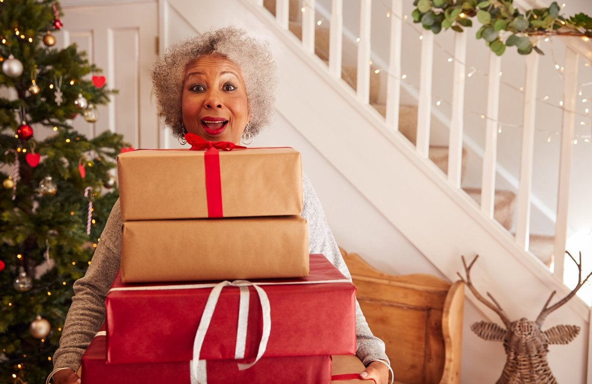 A woman standing in her decorated living room holding an armful of gifts.